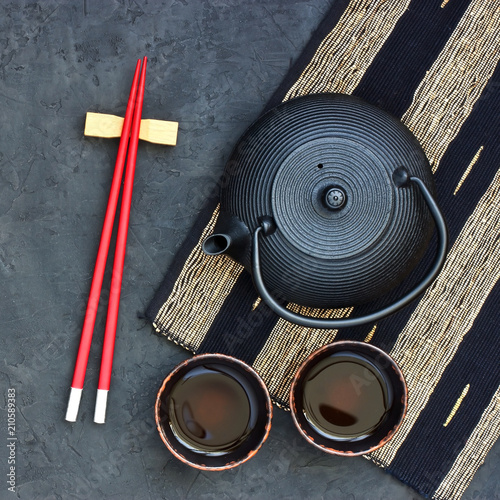 Fotografia  Black  teapot and tea cups on stone table