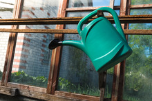 Green Watering Can Hanging In A Greenhouse At An Angle.