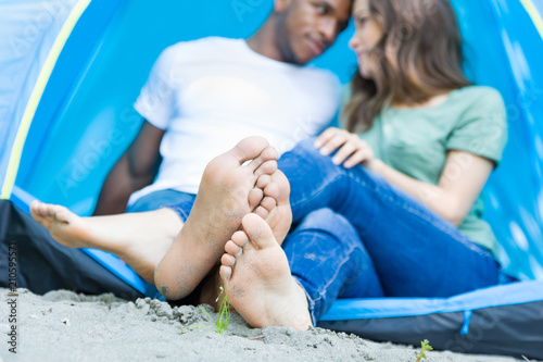 Barefoot Multiethnic Young Adult Couple Camping And Sitting In Tent Touching Feet Together