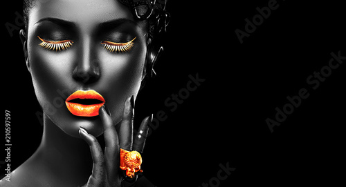 Poster Beauty Fashion model with black skin, golden lips, eyelashes and jewellery - golden ring on hand. Isolated on black background. Beauty woman face, beautiful make-up. Gorgeous lady fashion art portrait.