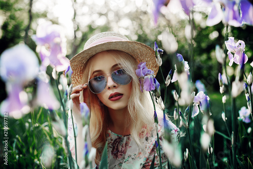 Outdoor close up portrait of beautiful woman wearing blue sunglasses, straw boater hat posing in the blooming garden