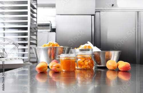 Jam from apricots in a glass jar on a polished stainless steel surface in pastry worktop