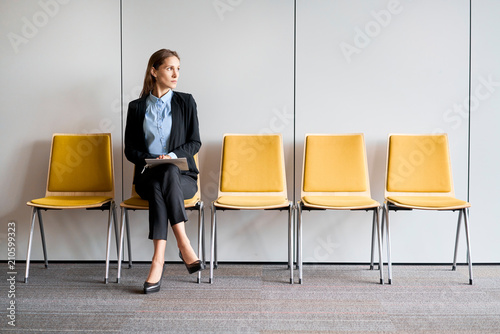 Fotografía  Young woman sitting in lobby with resume in hands and waiting for job interview
