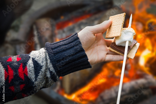Obraz Closeup of Hands Building Smore with Roasted Marshmallow and Chocolate At Campfire Outdoors - fototapety do salonu