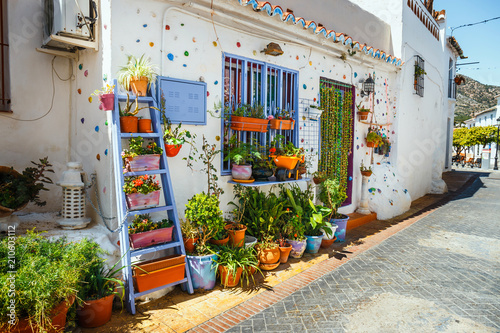 Photo decorated facade of house with flowers in blue pots in Mijas, Spain