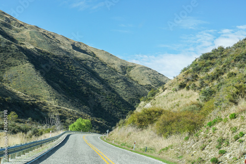 Tuinposter China travel and exploration concept - long curve concrete road along mountain range in New Zealand