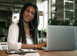 Closeup portrait of smiling young african woman sitting in a cafe with laptop