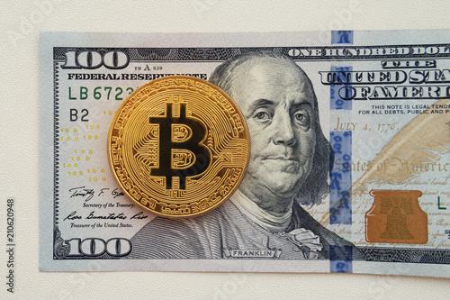Bitcoin on 100 dollar bill background  gold coin of bitcoin on a