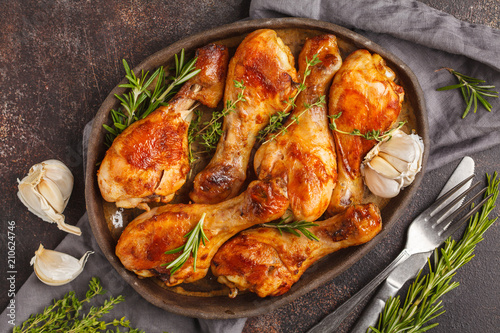 Fototapeta Grilled spicy chicken legs baked with garlic, rosemary and thyme on dark background. obraz