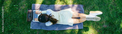 Obraz young pretty woman laying on blanket on green grass with laptop. overhead view - fototapety do salonu