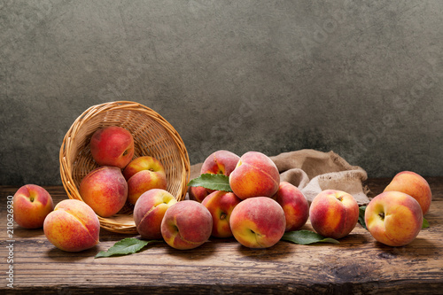 peaches with leaves in a basket on wooden table
