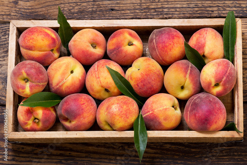 peaches with leaves in a wooden box, top view