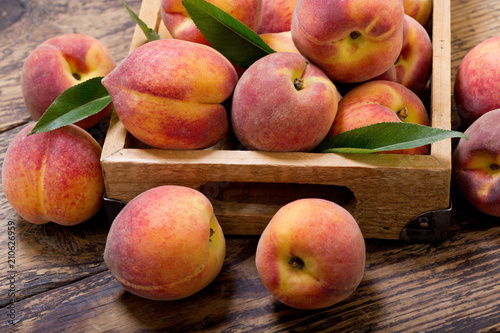 peaches with leaves in a wooden box