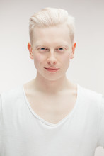 Albino Man With Hairstyle Dressed In Blank White T-shirt Looking At Camera Isolated Over White Backgrond. Mock Up Template For Design Print.