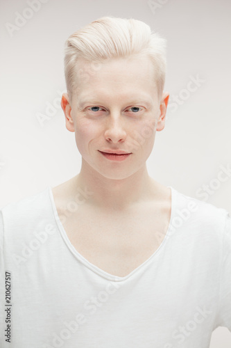 Photo Albino man with hairstyle dressed in blank white t-shirt looking at camera isolated over white backgrond