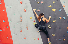 Back View Of Professional Climber Unrecognizable Woman Climbing On Practical Wall Indoor, Bouldering