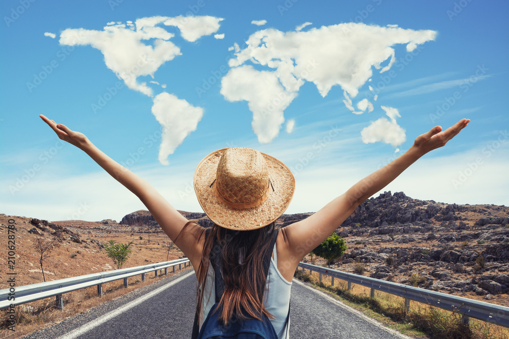Fototapeta Happy travel woman on vacation concept with world shaped clouds. Funny traveler enjoy her trip and ready to adventure.