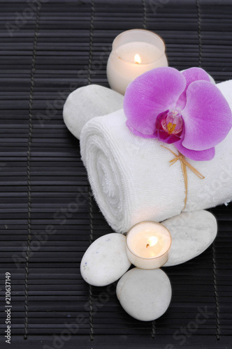 Spa setting with candle, rolled towel ,orchid, stones on on mat