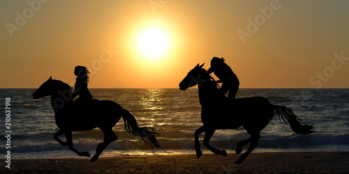 Leinwand Poster Two horse riders galloping on the beach