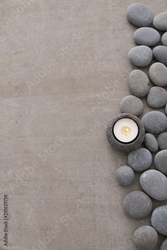 gray stones with white candle and grey background