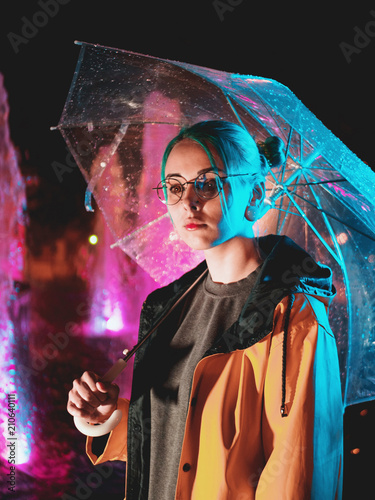 Acrylic Prints Young pretty girl with blue dyed hair in yellow raincoat and with transparent umbrella stands near fountain. Night neon illumination of city. Portrait of stylish hipster with glasses.