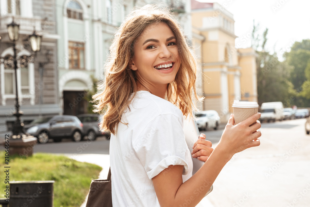 Fototapeta Portrait of smiling european woman strolling through city street with silver laptop, and takeaway coffee in hands