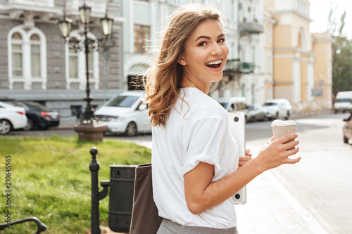 fototapeta na lodówkę Photo of pretty european woman walking through city street with silver laptop, and takeaway coffee in hands