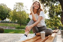 Image Of Smiling Modern Woman Sitting On Bench In Green Park On Summer Day, And Talking On Smartphone With Cup Of Takeaway Coffee