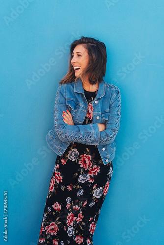 Fotografía lachende frau steht vor einer blauen wand und schaut zur seite