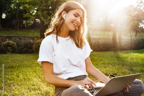 Portrait of attractive young woman sitting on green grass in park with legs crossed during summer day, while using laptop and wireless earphone - 210645946