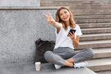 Fototapeta Na drzwi - European smiling woman sitting on street stairs with legs crossed on summer day, and showing peace sign with mobile phone in hand