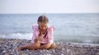 alone pretty little girl is wearing nice pink dress is sitting on a pebble beach near sea and playing