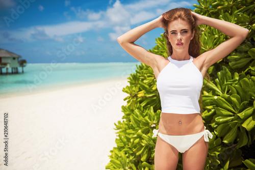 Beautiful young woman posing in sensual white swimwear at the beach Canvas Print