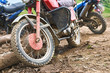 Offroad mountain motorcycles or bikes taking part in motocros competition parked on dirty terrain road with wooden logs