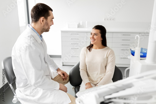 medicine, dentistry and healthcare concept - male dentist talking to female patient and discussing teeth treatment at dental clinic office
