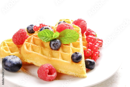 Cadres-photo bureau Nature Heart shape belgium waffles with assorted berries mix, strawberry, blueberry, raspberry and red currant decorated with mint leaf on white ceramic plate. Close up, copy space, background, top view.
