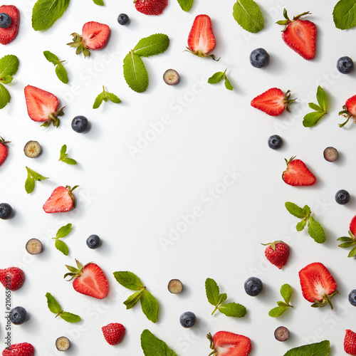 Frame of fruit pattern with strawberries, blueberries and mint leaves on a white background, flat lay Wall mural
