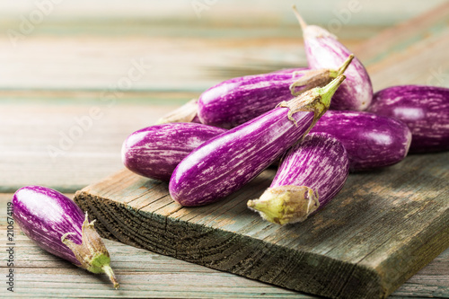 Heap of small eggplant or aubergine vegetable on old wooden background. Healthy food concept with copy space.