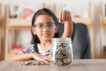 Asian Little Girl In Putting Coin In To Glass Jar Shallow Depth Of Field Select Focus At The Jar