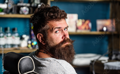 Man with beard and mustache sits in hairdressers chair, beauty supplies on background Tapéta, Fotótapéta