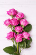 Bunch of pink roses flowers on white wooden background. F
