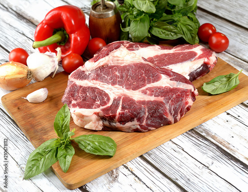 Photo sur Aluminium Viande fresh raw meat, herbs and spices on a cutting board on a wooden background