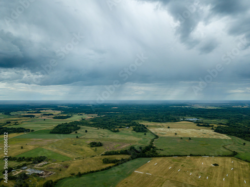 Foto op Aluminium Donkergrijs drone image. aerial view of rural area with houses and roads under heavy rain clouds