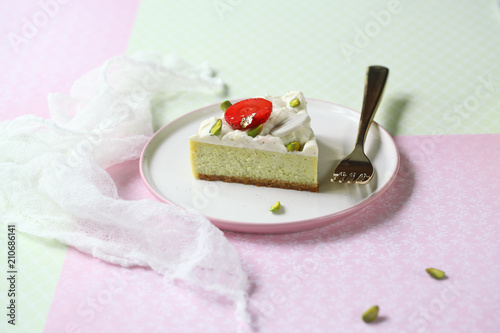 Cuadros en Lienzo Piece of Pistachio Cheesecake with Vanilla Diplomat Cream, on light green and pink background