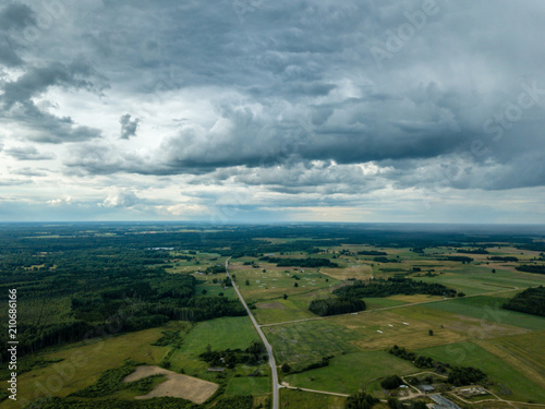 Poster Donkergrijs drone image. aerial view of rural area with houses and roads under heavy rain clouds