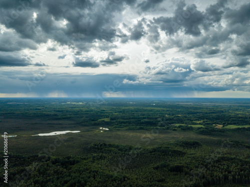 Tuinposter Blauwe jeans drone image. aerial view of rural area with houses and roads under heavy and dark dramatic rain clouds in summer day. night photo