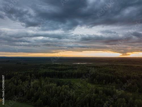 Foto op Canvas Zwart drone image. aerial view of rural area with houses and roads under heavy and dark dramatic rain clouds in summer day. night photo