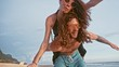 Close up portrait of a attractive young and energetic couple having fun on the beach. Woman piggyback riding a man and laughing. Sea Summer Vacation Happy Romantic Tourists concept