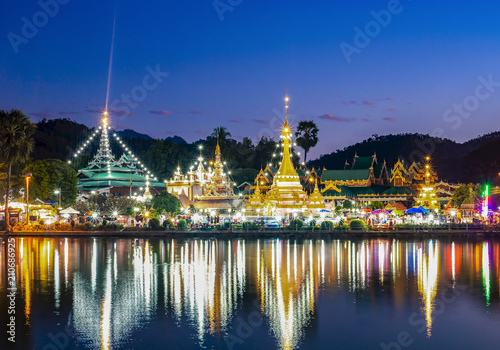 Night time view of Temple across  River in Thailand Poster