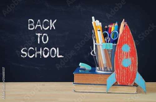 Fototapety, obrazy: Back to school concept. rocket and pencils over open book in front of classroom blackboard.